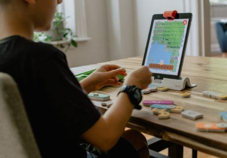 Young man coding using manipulatives learn math through coding