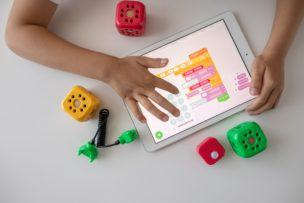 Best coding books for kids | Coderz childs arms on a tablet coding