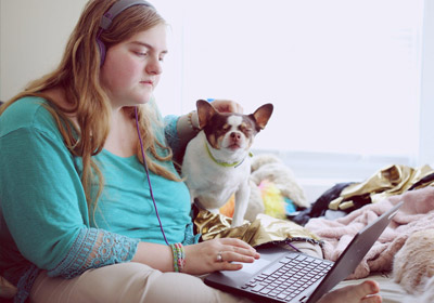 Woman with autism and dog on laptop coderz what is social emotional learning coding robotics